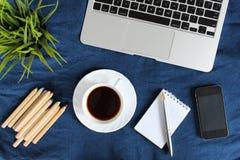 Teclado do portátil, copo branco do chá em pires, bloco de notas, pena e planta verde no canto na obscuridade - o azul amarrotou  foto de stock