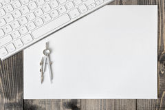 Teclado, documento y compás sobre tablón de madera Imagen de archivo