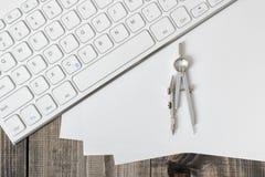Teclado, documento y compás sobre tablón de madera Imagenes de archivo