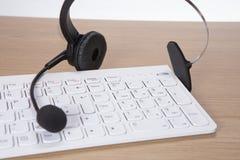 Teclado dos auriculares e de computador para o bate-papo em linha Foto de Stock Royalty Free