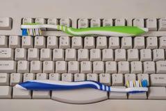 Teclado e escovas de dentes de computador. Fotografia de Stock