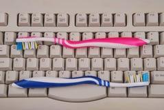 Teclado e escovas de dentes de computador. Foto de Stock