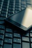 Teclado e telefone celular de computador em um bonito Fotografia de Stock Royalty Free