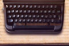 Teclado en una máquina de escribir del vintage en viejo fondo de papel Foto de archivo libre de regalías