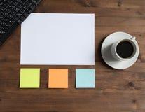 Teclado, etiquetas engomadas coloreadas y taza de café en el tablero Fotografía de archivo libre de regalías