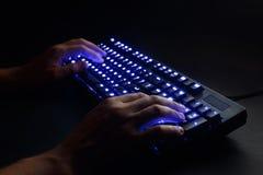 Teclado iluminado manos masculinas que mecanografían en un ordenador Fotografía de archivo