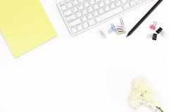 Teclado, libreta amarilla, flor del crisantemo, clips para los papeles, clips de papel y lápiz negro en un fondo blanco Concentra Fotografía de archivo