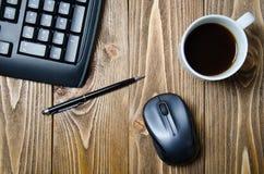 Teclado, pluma, ratón, y una taza de café en la tabla Fotos de archivo