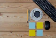 Teclado, taza coloreada de las etiquetas engomadas de café y materiales de oficina Fotografía de archivo libre de regalías