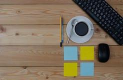 Teclado, taza coloreada de las etiquetas engomadas de café y materiales de oficina Fotos de archivo libres de regalías