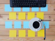 Teclado, taza coloreada de las etiquetas engomadas de café y materiales de oficina Imagenes de archivo