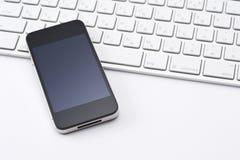 Teclado y smartphone Foto de archivo