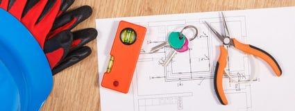 Teclas HOME com desenhos bondes, o capacete azul protetor com luvas e as ferramentas alaranjadas do trabalho, conceito da casa da Imagem de Stock