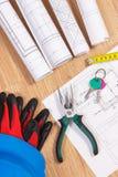 Teclas HOME con los diagramas o dibujos eléctricos, casco protector con los guantes y herramientas del trabajo, concepto casero c Fotos de archivo libres de regalías
