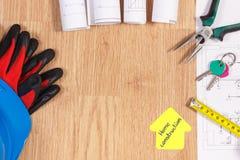 Teclas HOME con los dibujos eléctricos, el casco protector con los guantes y las herramientas del trabajo, concepto casero constr Imagen de archivo