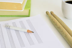 Teclee palillos, un lápiz y una hoja de música al lado de algunos libros y de una taza de café en un escritorio en una sala de cl Imagen de archivo libre de regalías