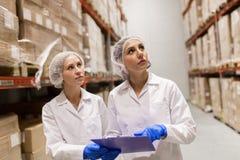 Tecnólogos de las mujeres en el almacén de la fábrica del helado Imagen de archivo libre de regalías