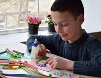 Tecnica di Quilling Ragazzo che fa le decorazioni o la cartolina d'auguri Strisce di carta, fiore, forbici Mestieri fatti a mano  Immagine Stock