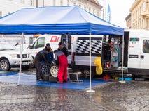 Tecniche che serviscono a riparazione delle automobili sportive le ruote sul grande quadrato nella città di Sibiu in Romania Fotografia Stock Libera da Diritti