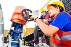 Tecnici che lavorano alla valvola in fabbrica o nell'utilità Fotografia Stock Libera da Diritti