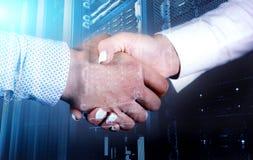 Tecnici che stringono le mani nella stanza al centro dati, doppia esposizione del server fotografie stock