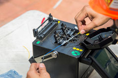 Tecnici che tagliano e cavi a fibre ottiche di fusione Immagine Stock Libera da Diritti
