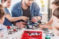 Tecnici occupati attenti che creano robot Fotografie Stock Libere da Diritti
