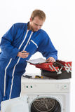Tecnician fixing a washing machine. Young plumber fixing a washing machine isolated on white background Stock Photos