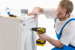 Tecnician fixing a washing machine. Young plumber fixing a washing machine isolated on white background Stock Photo