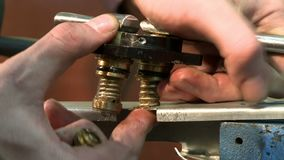 A man preparing gas equipment close up view. A tecnician twisting screw preparing gas equipment for hot air balloon indoor close up view stock footage
