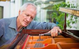 Tecnico anziano dello strumento di musica che sintonizza una tastiera di piano Immagine Stock