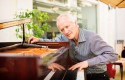 Tecnico anziano dello strumento di musica che sintonizza una tastiera di piano Immagine Stock Libera da Diritti