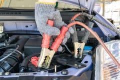 Tecnico automobilistico che carica la batteria del veicolo immagine stock libera da diritti
