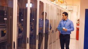 Tecnico che cammina nella stanza del server stock footage