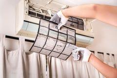 Tecnico che indica il filtro dal condizionatore d'aria in pieno del du bloccato fotografia stock