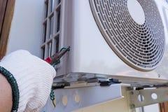 Tecnico che installa l'unità di condizionamento d'aria all'aperto Fotografie Stock