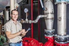 Tecnico che ispeziona il sistema di riscaldamento in caldaia fotografia stock