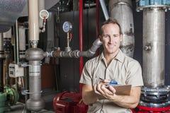Tecnico che ispeziona il sistema di riscaldamento in caldaia immagini stock libere da diritti