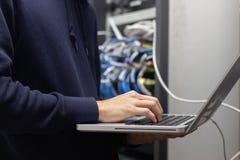 Tecnico che lavora al computer portatile nella stanza del server, mani che scrivono testo a macchina o immagini stock libere da diritti