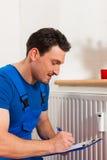 Tecnico che legge il contatore di calore Immagine Stock Libera da Diritti