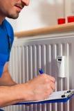 Tecnico che legge il contatore di calore Fotografia Stock