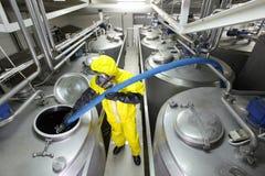 tecnico che riempie grande serbatoio d'argento in fabbrica Fotografia Stock