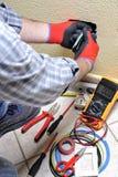 Tecnico dell'elettricista sul lavoro con l'attrezzatura di sicurezza su un sistema elettrico residenziale fotografia stock libera da diritti