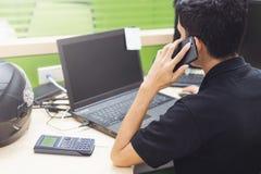 Tecnico della progettazione senior che utilizza telefono cellulare mentre lavorando circa l'organizzazione nel fuoco selettivo ca Immagine Stock