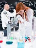 Tecnico di laboratorio che guarda giù un microscopio immagini stock