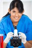 Tecnico di laboratorio che per mezzo del microscopio Fotografie Stock Libere da Diritti