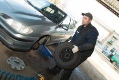 Tecnico di manutenzione sul lavoro del pneumatico Immagini Stock Libere da Diritti