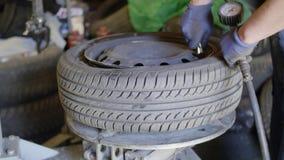 In tecnico esperto dell'automobile pompa sulla gomma sulla ruota nell'esterno di servizio di riparazione automatica archivi video