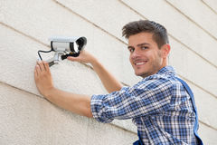 Tecnico Fixing Cctv Camera sulla parete Fotografia Stock