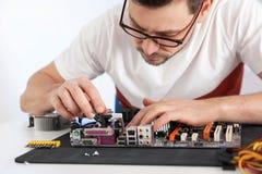 Tecnico maschio che ripara scheda madre alla tavola immagini stock libere da diritti